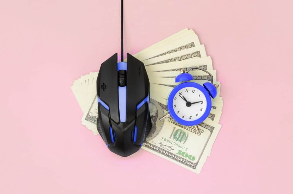 Computer mouse and small violet alarm clock on many dollar bills