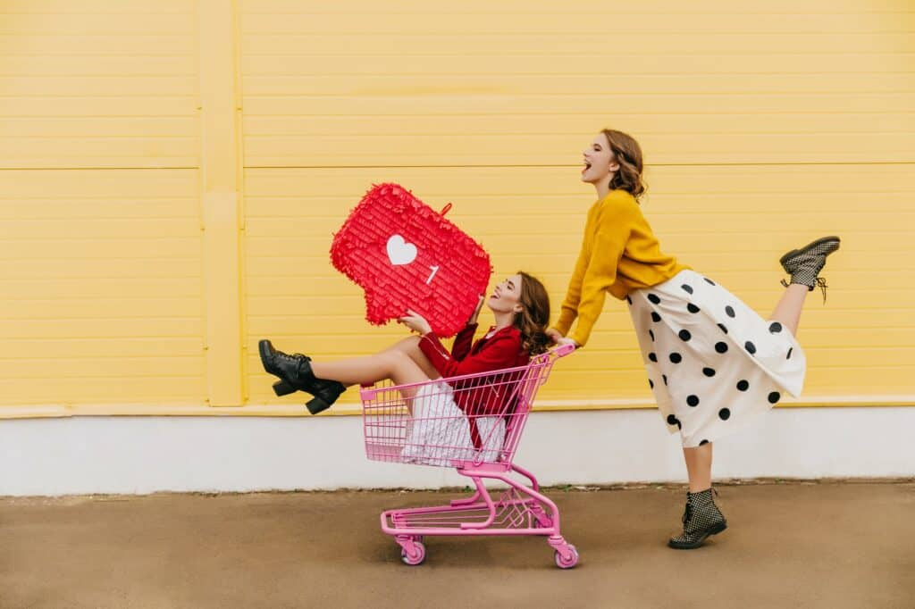 Half length shot of two girls with instagram like icon. Outdoor photo of female models using shopping cart